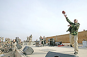 """David Letterman tosses footballs to servicemembers during """"The Late Show"""" at Camp Taqaddum, Iraq, December 24, 2004. Letterman, along with his musical director Paul Shaffer and stage manager Biff Henderson, brought the popular late night television show to the Marines, sailors and soldiers currently stationed at Camp Taqaddum, Iraq. They were followed with a performance from """"Off the Wall,"""" a southern California band, which added to the holiday festivities. .Mandatory Credit: Luis R. Agostini / USMC via CNP."""