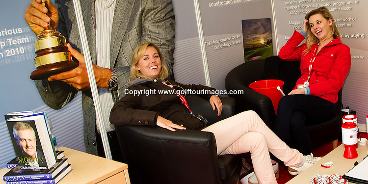 The Elizabeth Montgomerie Foundation team of Lauren Bryden ( brown jacket) and Lynsey Knowles ( red jacket ) take time out after a hectic day of visitors to their stand at Golf Live 2012 where Colin Montgomerie signed autographs and  - Golf Live took place at The London Club, Brands Hatch, Kent from 18th to 20th May 2012: Picture Stuart Adams www.golftourimages.com: 20th May 2012