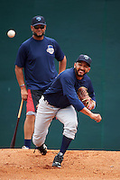Mobile BayBears pitcher Gabriel Arias (20) throws in the bullpen as pitching coach Wellington Cepeda watches during practice before a game against the Mississippi Braves on April 28, 2015 at Hank Aaron Stadium in Mobile, Alabama.  The game was suspended after the top of the second inning with Mobile leading 3-0, the BayBears went on to defeat the Braves 6-1 the following day.  (Mike Janes/Four Seam Images)