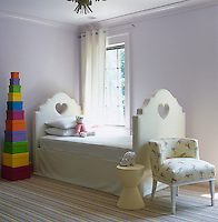 A stack of brightly coloured boxes forms a tower next to the bed in this child's bedroom