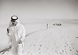 SAUDI ARABIA, man wearing a traditional Thobe and smoking in The Empty Quarter, Najran (B&W)