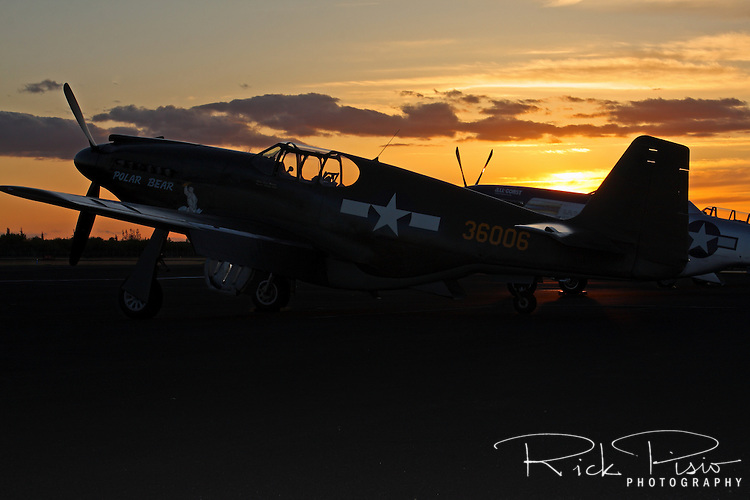 A North American P-51A Mustang sits on the ramp at sunset.