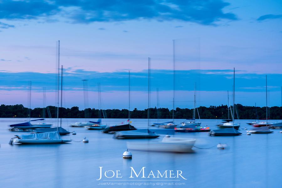 Blurred sailboats at dawn on Lake Harriet in Minneapolis, Minnesota.