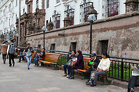 Peru, Cusco.  Peruvians Relaxing Mid-day in front of City Hall, the Palacio de Justicia.