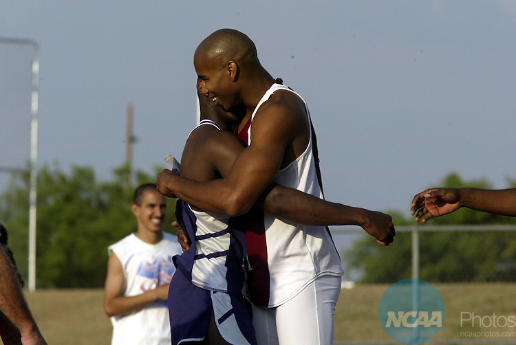 25 May 2002:   Jason Cornelius of Morehouse (right) hugs competitor Terrance Woods of Abilene Christian University (in blue) after Jason won the men's high jump during the NCAA Division II Men's Track and Field Championships held on the campus of Angelo State University in San Angelo, TX. Michael Vosburg / NCAA Photos