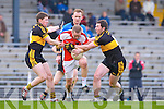 Dr Crokes Kieran O'Leary left and Daithi Casey tackles Rathmore's Conor O'Sullivan closely watched by referee Mike Brosnan during the O'Donoghue Cup final in Fitzgerald Stadium on Sunday
