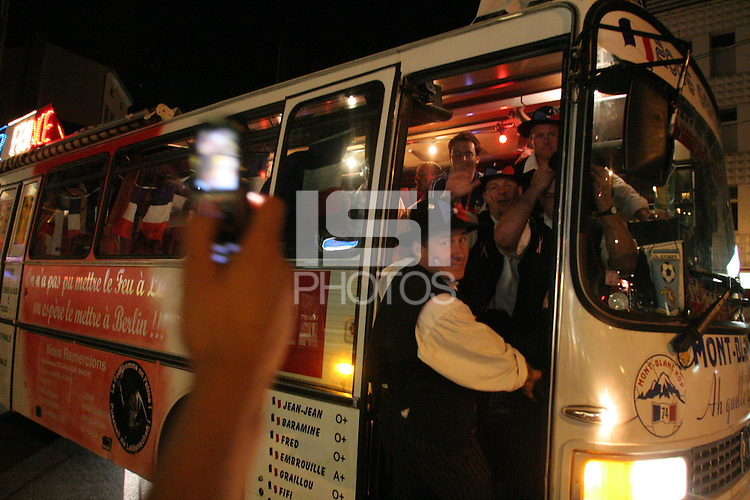 A man with a cell phone camera takes a photograph of a bus full of French National soccer team supporters celebrating in downtown Hannover  after France and Spain's  second round FIFA World Cup match in Hannover, Germany  on Tuesday, June 27th 2006.  France defeated Spain 3-1.