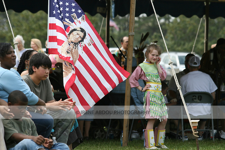 A young jingle dancer stands next to a Native American flag at the 8th Annual American Indian Pow Wow in Virginia Beach, Virginia.