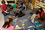 Education Elementary School Grade 4 class working on floor with paper cut into pieces to represent fractions mathematics lesson hands on learning horizontal