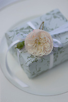 A pale pink rose tucked into white ribbon is the finishing touch to an elegantly gift-wrapped box