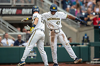 Michigan Wolverines designated hitter Jordan Nwogu (42) celebrates with teammate Jimmy Kerr (15) after scoring during Game 1 of the NCAA College World Series against the Texas Tech Red Raiders on June 15, 2019 at TD Ameritrade Park in Omaha, Nebraska. Michigan defeated Texas Tech 5-3. (Andrew Woolley/Four Seam Images)