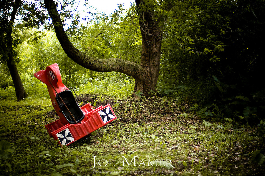 Toy replica airplane nose dives into green forest.