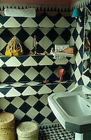 The small bathroom is decorated with black and white checked tiles