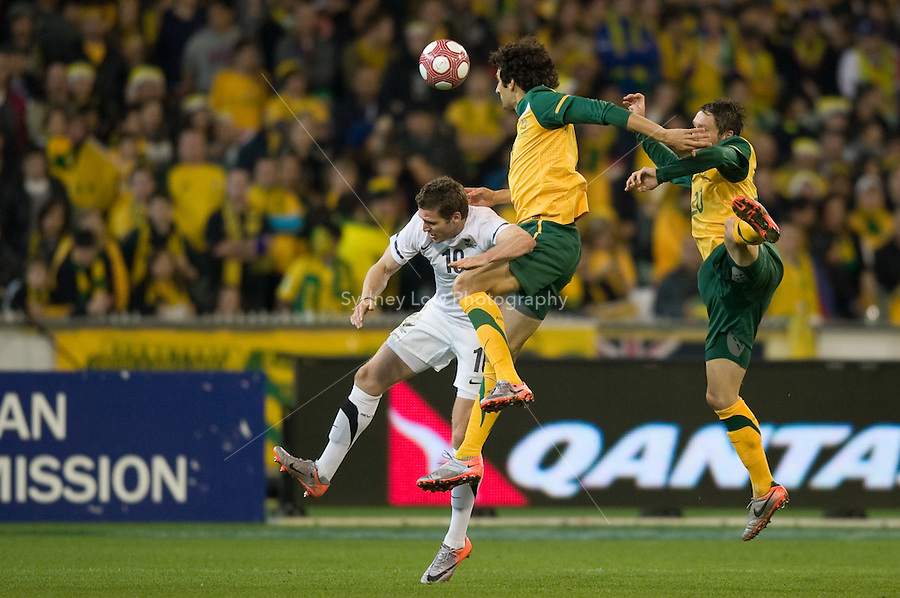 MELBOURNE, AUSTRALIA - MAY 24, 2010: Mile Jedinak of the Qantas Socceroos jumps over Chris Killen of New Zealand at the FIFA World Cup farewell match between Australia and New Zealand at the Melbourne Cricket Ground, 24 May, 2010 in Melbourne, Australia. Photo by Sydney Low / www.syd-low.com