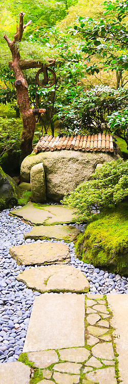 Stone walkway  with river stones leads to well in Portland Japanese Garden strolling garden.  Lantern seen in background amoung trees and rhododendrons and azaleas in panoramic format.