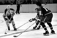 Seals Tony Featherstone against Canucks John Schella and Rich Lemieux. (1971 photo by Ron Riesterer)