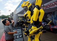NWA Democrat-Gazette/JASON IVESTER<br /> Anthony Almaraz, 9, of Rogers greets Transformers character Bumblebee Monday, June 12, 2017, outside the Wal-Mart Supercenter on Walnut Street in Rogers. The character is part of a five-month tour around Wal-Mart stores promoting the upcoming movie, Transformers: The Last Knight, which releases later this month. The tour will make stops at Wal-Mart stores in Fort Smith on Thursday and the Wal-Mart on Martin Luther King Jr Boulevard in Fayetteville on Thursday at 5:30.