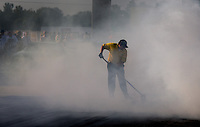 Aug. 30, 2013; Clermont, IN, USA: A member of the NHRA safety safari scrapes the track as burnout smoke covers the starting line during qualifying for the US Nationals at Lucas Oil Raceway. Mandatory Credit: Mark J. Rebilas-