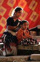 An Indian woman dresses her daughter's hair. Bangalore, India.