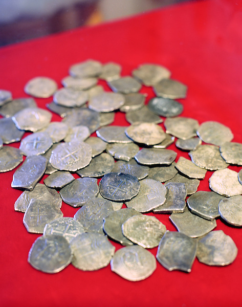 """PROVINCETOWN,MASSACHUSETTS : Spanish coins salvaged from the wreck of the pirate ship Whydah. Barry Clifford, America's top underwater archaeologist an explorer.  In 1984, underwater explorer Barry Clifford and his Project Team discovered the site of the 1717 shipwreck of the Whydah off Cape Cod, the only verified pirate shipwreck ever discovered. The Whydah, built as a slave ship in 1715 and captured by pirate Capt. """"Black Sam"""" Bellamy two years later. The Whydah sank in a ferocious storm off Cape Cod in 1717, killing Bellamy and all but two of the 146 men on board. Using historical research, remote-sensing techniques and underwater surveys, Clifford has been involved in the survey and/or recovery of numerous other shipwrecks. They include more than 50 wrecks around Cape Cod, various 17th and 18th century wrecks in the Indian Ocean, more than 20 wrecks in New York's East River, and others in Florida, the Bahamas, the Bay of Corinth, Boston, Belize and Panama..Provincetown, Cape Cod , Massachusetts. USA"""