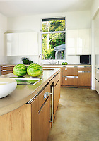 The vibrant green of the watermelons on the kitchen worktop mirrors the green of the vegetation outside the window