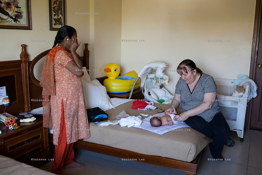 Idan (left), the surrogate who just gave birth to Barbara's baby, prepares to leave after breastfeeding the baby in Barbara's hotel room near the Akanksha Clinic in Anand, Gujarat, India on 11th December 2012. Barbara, from Canada, had come to receive him at his birth from Idan, her surrogate, and is waiting for her husband to come and join her in Anand, while she continues to hire Idan to breastfeed her son. Idan's husband sends pumped breast milk to Barbara's hotel in the evenings when Idan cannot come personally. Photo by Suzanne Lee / Marie-Claire France