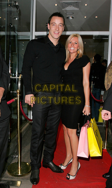 JOHN TERRY & TONI POOLE.The White Room - charity fundraiser, Flawless & Co, New Bond Street, London, England..November 8th, 2007.full length black dress trousers shirt couple goody bag  .CAP/AH.©Adam Houghton/Capital Pictures.