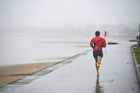 Swansea, Wales :- Friday 23rd January 2015 ... <br /> <br /> A runner braves the wet windy weather in Swansea, running along the promenade during a miserable January.