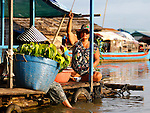 WOMAN FISHING  IN CHONG KOS FLOATING VILLAGES AT TONLE SAP RIVER