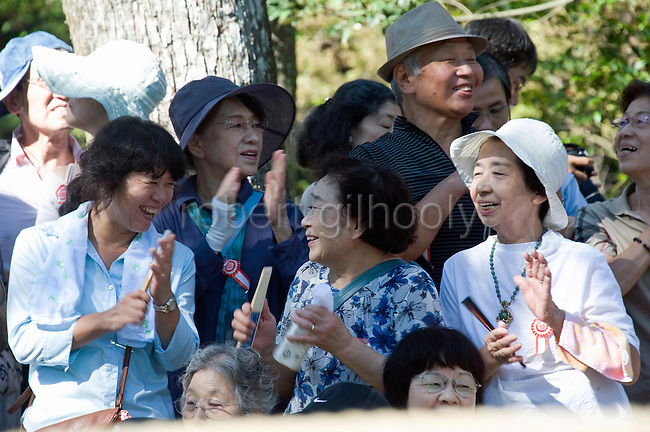 """Members of the public react after a mounted archer hits his target during the """"yabusame-shinji"""" mounted archery ritual on the 3-day Reitaisai grand festival in Kamakura, Japan on  16 Sept. 2012.  Thousands turn up to the festivals main attraction, during which archers ride at speed and attempt to hit three targets along a 250-meter course erected inside the shrine grounds. Photographer: Robert Gilhooly"""