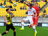 Keegan Smith punches the ball away under pressure from Johan Absalonson during the A-League football match between Wellington Phoenix and Adelaide United FC at Westpac Stadium in Wellington, New Zealand on Sunday, 8 October 2017. Photo: Dave Lintott / lintottphoto.co.nz
