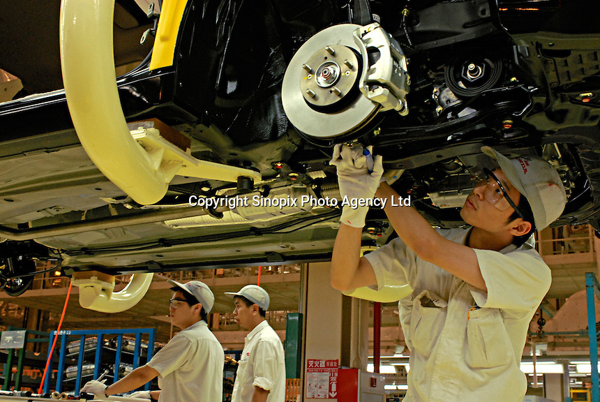A worker on the production line of the Honda Accord at the new Guangzhou Honda Automobile Co. Ltd. factory. The plant built at a cost of 140 million US$ is one of the most advanced car plants in the world. It has a state of the art production line as well as the world's first total water re-cycling sytem..
