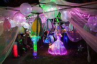 Magical sheer fabric canopy art installation, covered with neon lights and balloons at night, Arts-A-Glow Festival, Dottie Harper Park, Burien, WA, USA.