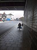 Elderly woman with shopping bags walks under a railway bridge in Cricklewood, London.