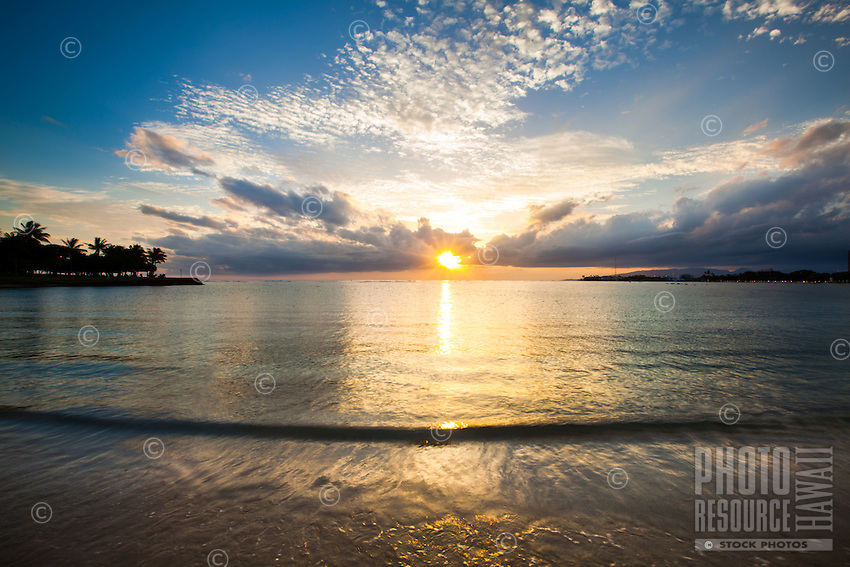 A calm and contemplative sunset view at Ala Moana Beach, Honolulu, O'ahu.