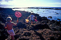 Kids with fishing nets scramble over the rocks at Shark's Cove, North Shore, Oahu.