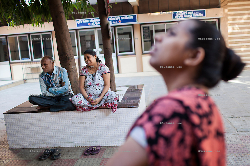 Leela Mekwan (center), 34, sits with her husband Jayantibhai (left), 38,  as a nurse, Sejal Parmar, 32, looks on in the Akanksha IVF and surrogacy center in Anand, Gujarat, India on 9th December 2012. Leela is 9 months pregnant with her 2nd surrogacy that she is doing with Dr. Nayana Patel and has support from her immediate family including her 2 sons. Photo by Suzanne Lee/Marie-Claire France