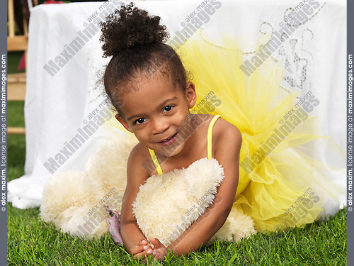 Portrait of a cute smiling three year old black girl at a party wearing a yellow tutu dress