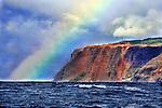 A colorful rainbow can be seen rising over the Napali Coast in Kauai, Hawaii.