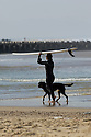 Girl with longboard + dog on the beach in Hossegor, France.