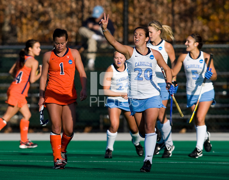 Caitlin Van Sickle (20) of UNC celebrates a goal as  Tara Puffenberger (1) of Virginia walks back to midfield during the NCAA Field Hockey Championship semfinals in College Park, MD.  North Carolina defeated Virginia, 4-3, in overtime.