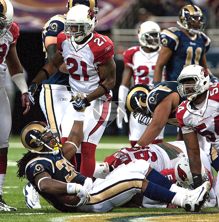 112209tvhandup.Cardinals safety Antrel Rolle (21, center standing) gives a hand up to Rams RB Steven jackson (39, on ground) after Jackson was tackled by multiple Cardinals defenders in the third quarter..BND/TIM VIZER