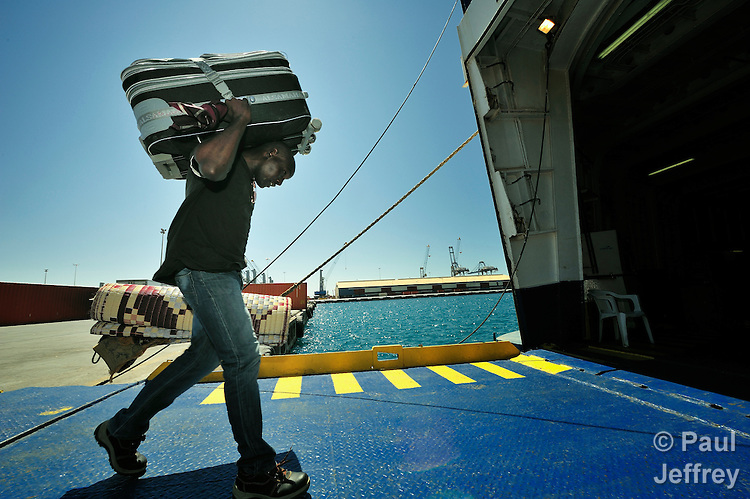 An African worker walks aboard a ferry on the dock in Misrata, the besieged Libyan city where civilians and rebel forces are surrounded on three sides by forces loyal to Libyan leader Moammar Gadhafi. Thousands of migrant workers are fleeing the war, most returning to their homes in Niger, Chad, and Sudan.