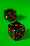 Pair of black dice isolated on green background