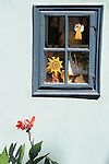 A small window on a light blue house in the Golden Lane in Prague Castle in Prague, Czech Republic.
