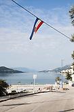 Eine kroatische Flagge hängt über einer Straße in Neum. Der kleine Ort Neum liegt in Bosnien-Herzegovina und bildet den einzigen Zugang zum Meer des Balkanlandes. Auf einer Länge von 9 km durchschneidet der Ort das kroatische Staatsgebiet (Neum-Korridor) Seit dem EU-Beitritt Kroatiens ist Neum auf beiden Seiten von EU-Außengrenzen eingeschlossen. / A Croatian flag hangs above a street in Neum. The small city of Neum in Bosnia and Herzegovina is the only place in Bosnia, where the country has access to the adriatic sea. Over a length of 9 kilometers the area cuts Croatian territory in two pieces. Since Croatia became part of the European Union, the city of Neum is enclosed between two EU-boarders.