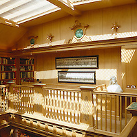 One oak-panelled wall in the gallery library is suffused in filtered sunshine through the louvred skylight