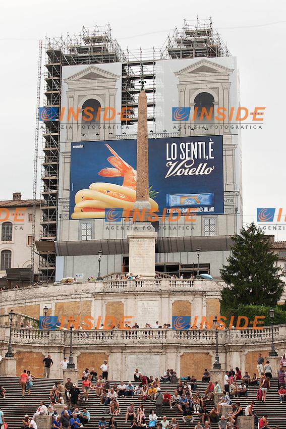 Via Condotti e sullo sfondo Trinita' de' Monti, coperta dalla pubblicit&agrave;' della Voiello, che ha destato una grande polemica su Twitter con l'ashtag #Voiellolevalo<br /> Via Condotti and in the background the spanish steps covered by a huge poster of Voiello, which has created a controversy on Twitter<br /> Roma 22-09-2014 Piazza di Spagna. Riapertura della fontana del Bernini detta la 'Barcaccia' completamente restaurata.<br /> Reopening of the Bernini's Barcaccia fountain in Spagna Square, just at the bottom of the Spanish Steps, after its closure for restoration.<br /> Photo Samantha Zucchi Insidefoto