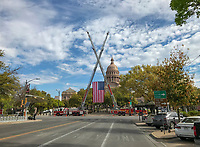 A glorious site to see the Austin Fire Department fire engine cranes frame the US Flag in front of the Texas State Capitol on a beautiful spring day in sunny Austin, Texas.