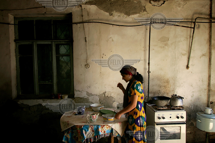 A woman prepares a meal in the kitchen of her house.